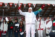 Grand Forks torch bearer, Jock MacKay, proudly holds the flame on stage while the Sopranos sing O Canada; Photo, Mona Mattei