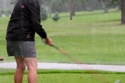 Grand Forks resident Colleen Verigin lines up on the first hole while the rain pours over her. Photo Erin Perkins.