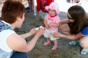 Taya Mack, 18 months old, happily accepts a kid-sized Canada Day cupcake from Shelly Ball at the Christina Lake festivities. Photo Erin Perkins.