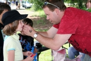 There were lots of free activies for the kids at Christina Lake including a fishing game, face painting and fake tattoos like this one being put on child's cheek. Photo Erin Perkins.