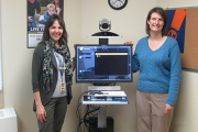 Paula Smith (R), standing with renal nurse Georgi Winger and the telehealth unit in Cranbrook, no longer has to drive to Trail for her appointments. — Photo courtesy IHA